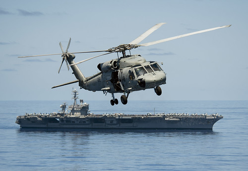 A helicopter flies past USS Carl Vinson. by Official U.S. Navy Imagery