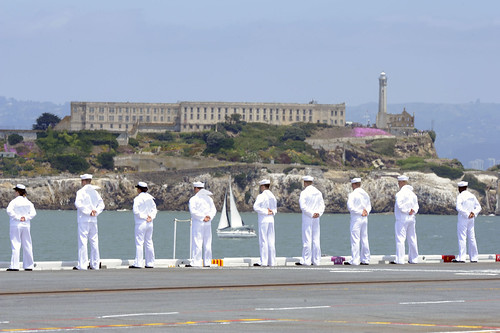 Sailors aboard USS Nimitz man the rails as it passes Alcatraz Island in San Francisco Bay. by Official U.S. Navy Imagery