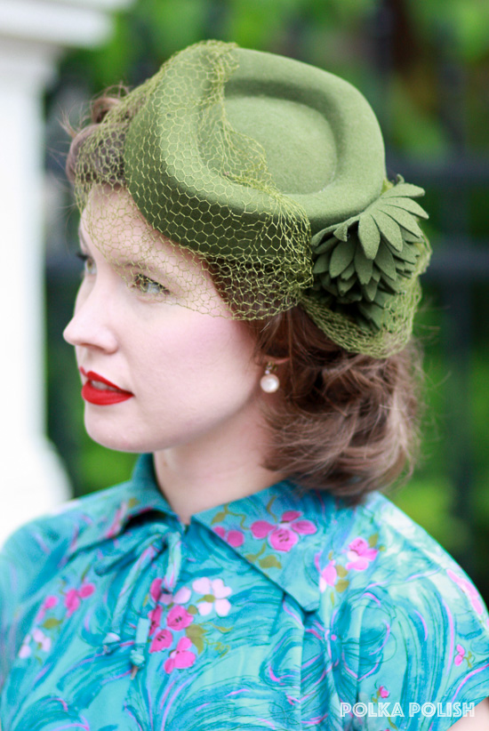 A smart green 1940s tilt hat is decked out with felt flowers and a veil