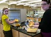 Two girls work in a chemistry lab with their hands in a gooey, yellow substance.