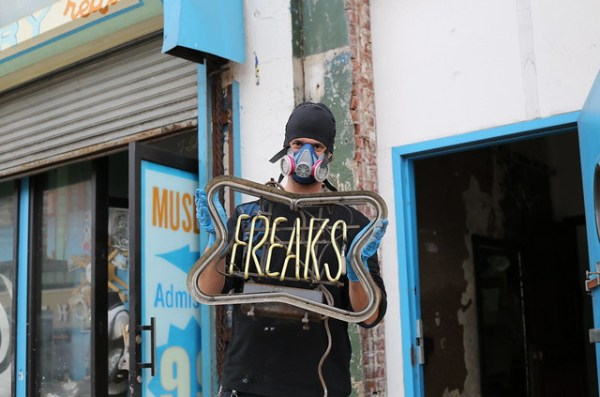Man holding neon Freaks sign after Hurricane Sandy