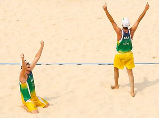 two men playing beach volleyball in loose tank tops and long shorts. Their arms are up, as in a victory pose.