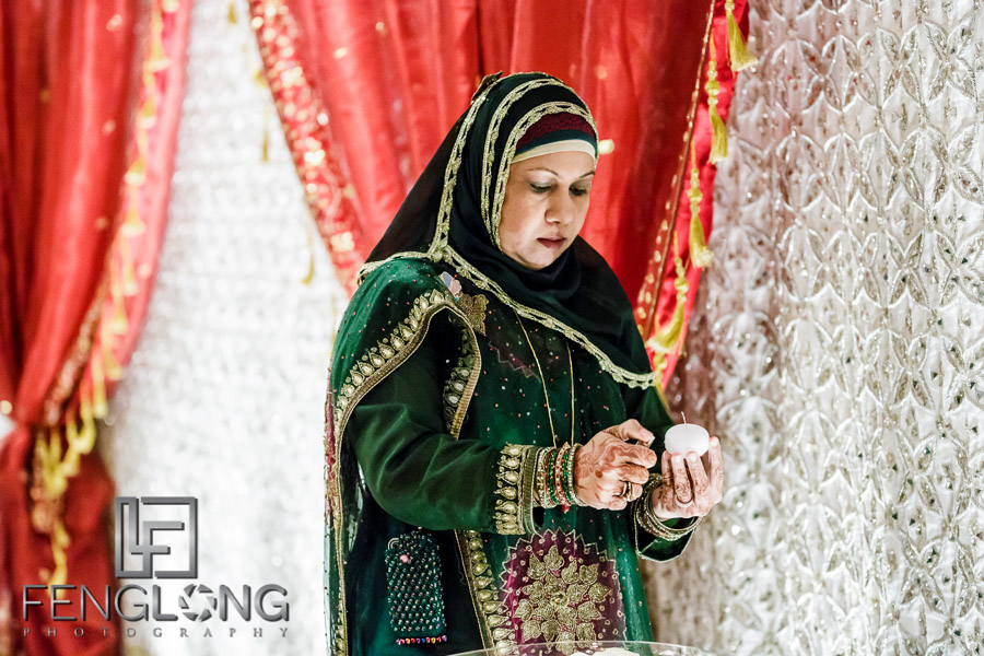 Muslim woman lighting candles for wedding ceremony