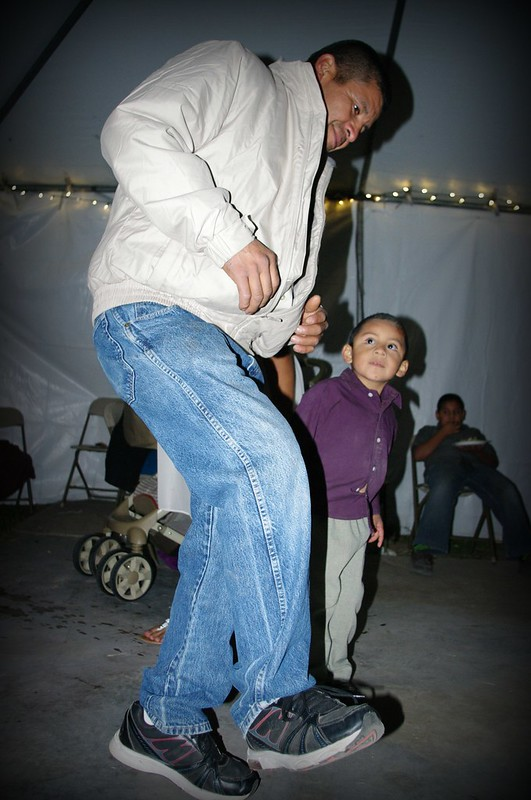 A young boy looks up at his Father who has just begun to dance.