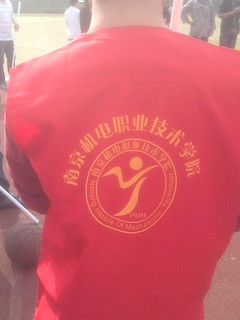 A red tabard with the name and logo of the Nanjing Institute of Mechatronics Technology in Chinese and English.