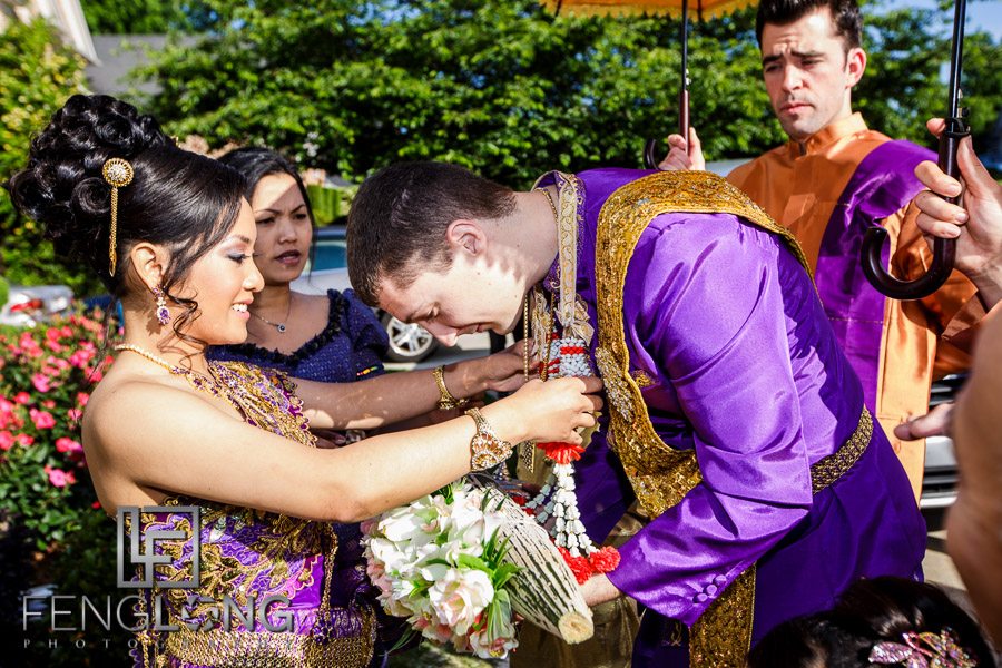 Cambodian bride places flower wreath on American groom