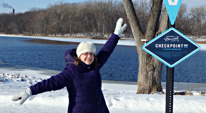 a smiling woman in a purple winter coat with her arms outstretched