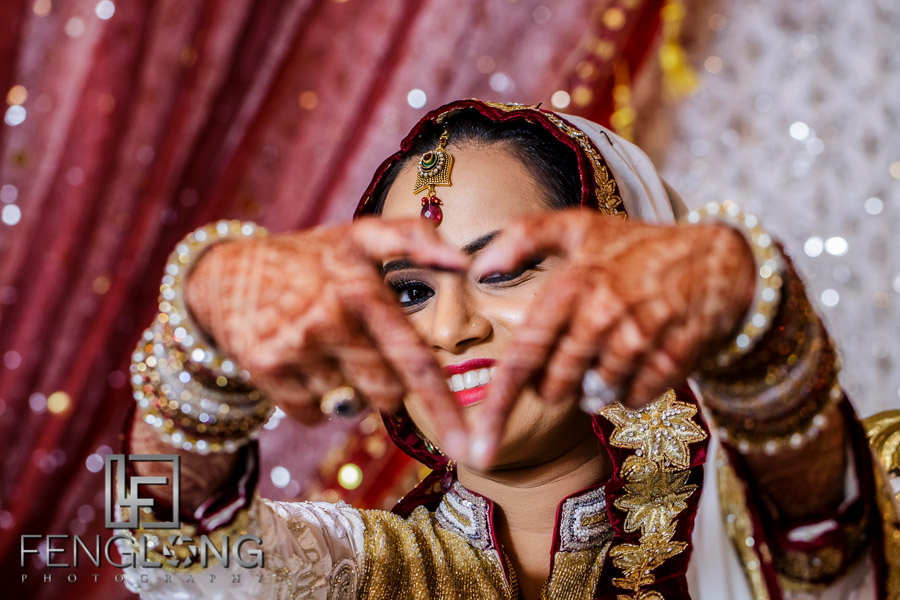 Indian bride making heart sign with hands showing off henna design