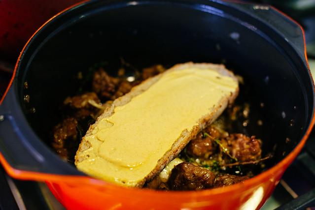 Gestoofde varkenswangen met bier, brood en mosterd.