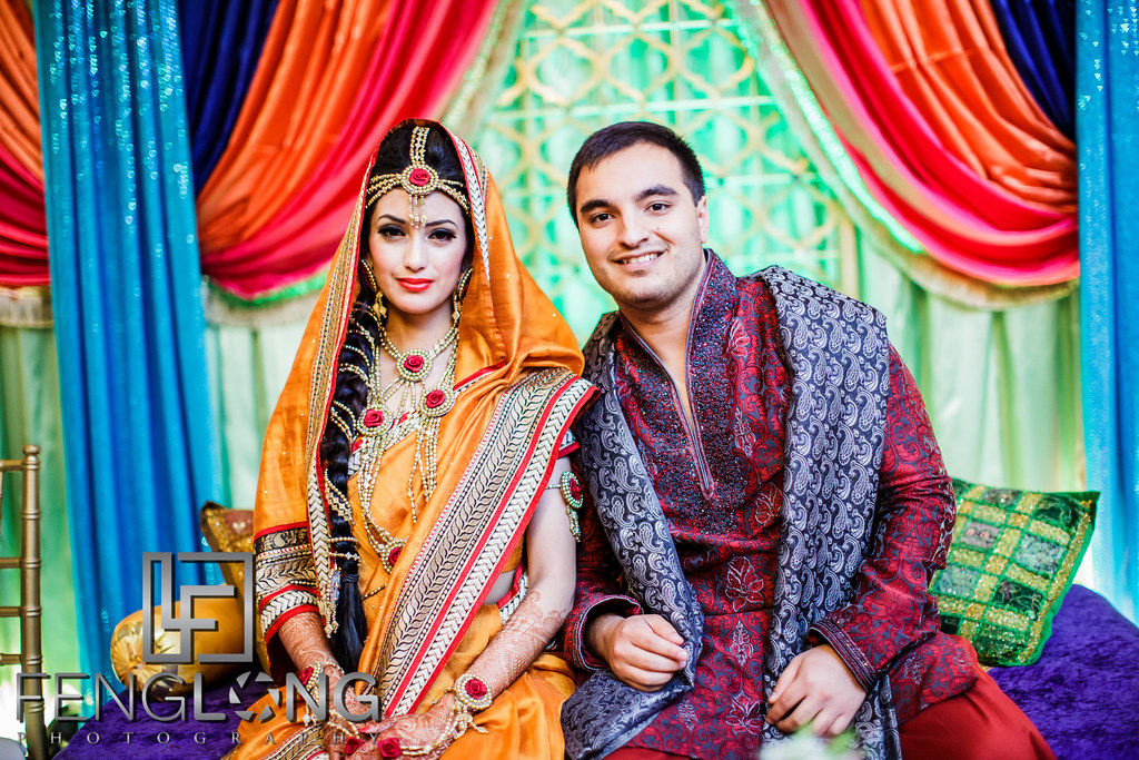 Bengali Bride and Pakistani groom pose for a photo on stage during Mehndi night