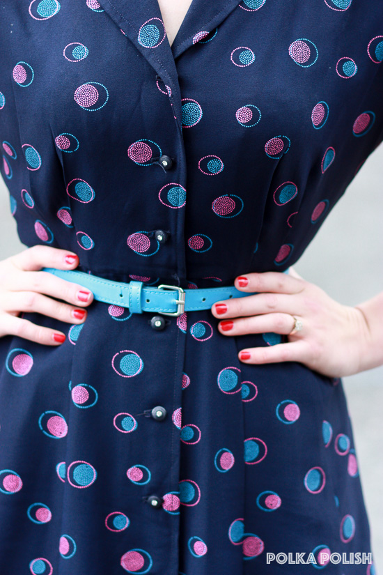 Detail of a 1940s navy day dress.  The pattern is pink and teal polka dots made up of even smaller polka dots