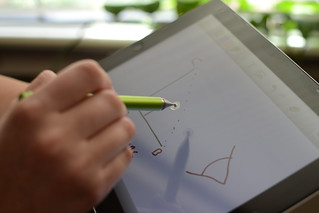 hand writing math notes with a green stylus on a tablet computer