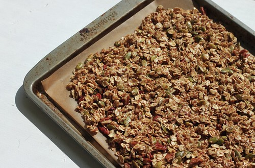 3/4 view of a baking pan lined with parchment and covered with a thin layer of granola, sans blueberries.