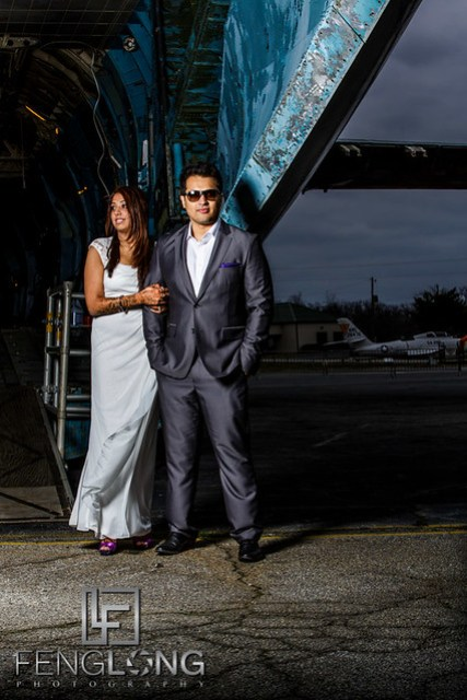 Indian bride and groom posing for pre-wedding photos outside airplane cargo bay