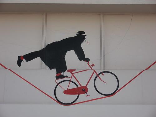 Nemo le funambule en équilibre sur un fil, Ménilmontant à vélo, Paris, Street Art