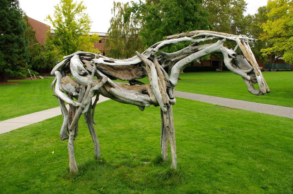A full size sculpture of a horse made entirely out of driftwood pieces.