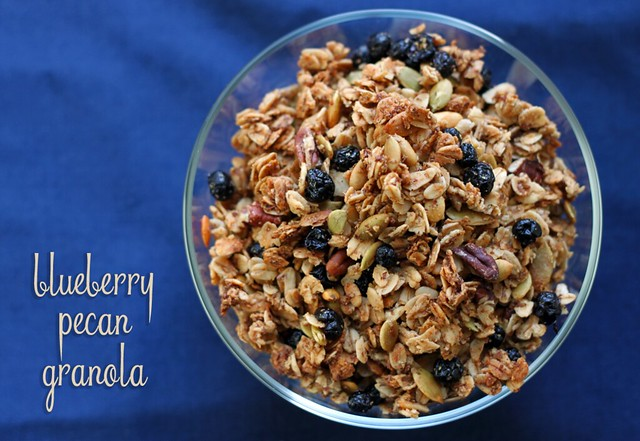 Top-down view of a small glass bowl filled with granola, dotted with pecans, sunflower seeds, and dried wild blueberries.