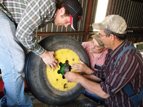 Kurt, Carl, and Dad fix a wheel on the planter