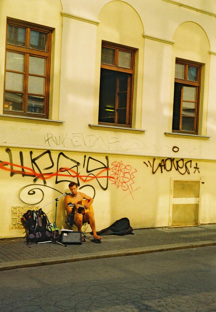 Street Musician under the Scrawl (redscale film)