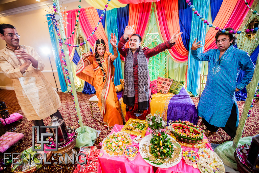 Bride and groom dance on stage during entrance on Mehndi night