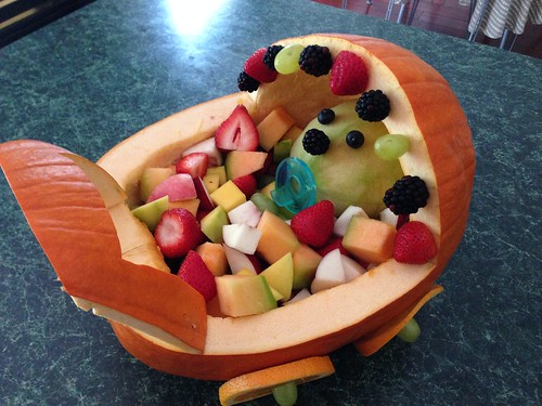 Pumpkin baby carriage with cut fruit and a cantaloupe baby head