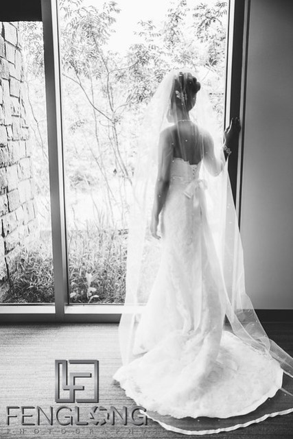 Cambodian bride in American wedding dress looks out the window