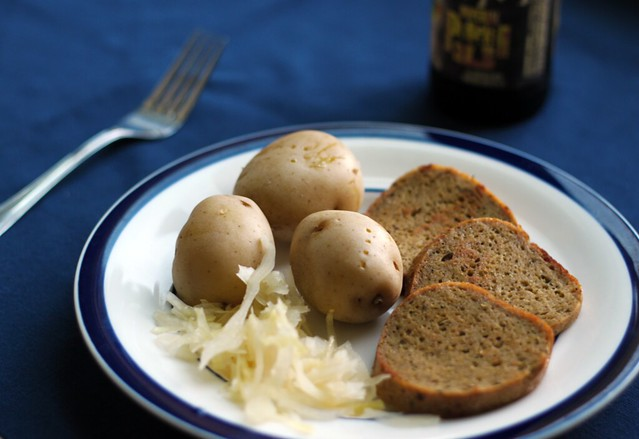 Three-quarter length view of a white plate with three slices of sausage, three small boiled golden potatoes, and a pile of sauerkraut. In the background is a bottle of pumpkin beer.