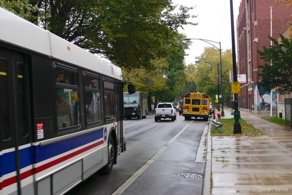 CTA bus has to wait because illegally parked vehicles on both sides make it too narrow to pass