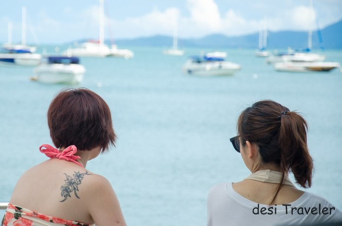 Woman with tatto on shoulder boats in ocean
