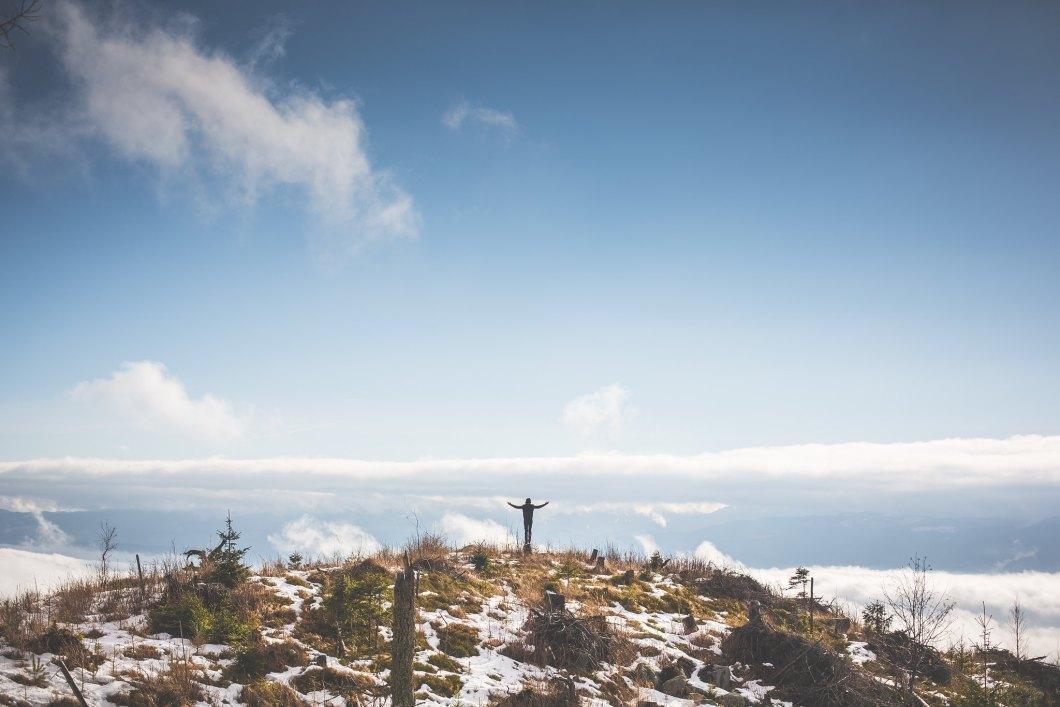 Imagen gratis de un hombre con los brazos abiertos en una montaña