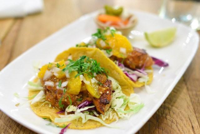 Tacos de Pescado al Pastor Two tacos of seared fish in ancho chile adobo, orange, onion, cilantro and salsa de morita y tomatillo