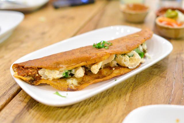 Quesadilla Roja con Chicharrón Mulato chile-corn tortilla, crispy pork belly, salsa cascabel, jack cheese, queso fresco, onion and cilantro