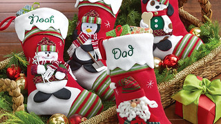 Personalized Stockings from Personal Creations with a snowman, Santa, a penguin and a dog in a basket with pine cuttings, ornaments and a small wrapped gift with a green bow