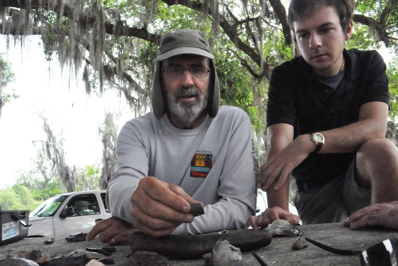 Prior to wading into the chest-high deep water of the Peace River, Mark Renz of Fossil Expeditions reviews some of the fossils we may find while his assistant, Kyle, looks on. March 2015