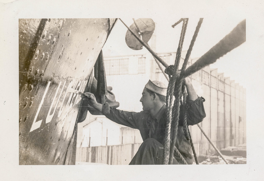 Sailor painting the name on the side of a ship