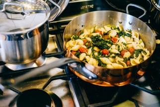 Preparing pasta con cime de rape e pomodori