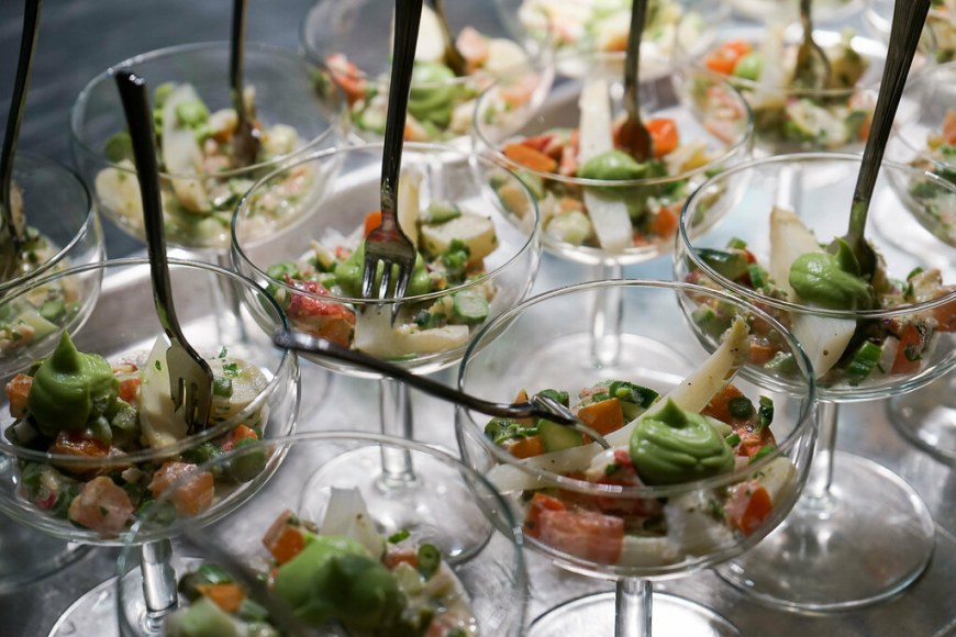 A sample of ceviche with avocado mouse on top, served in a glass. The picture is showing many glasses filled with the ceviche.