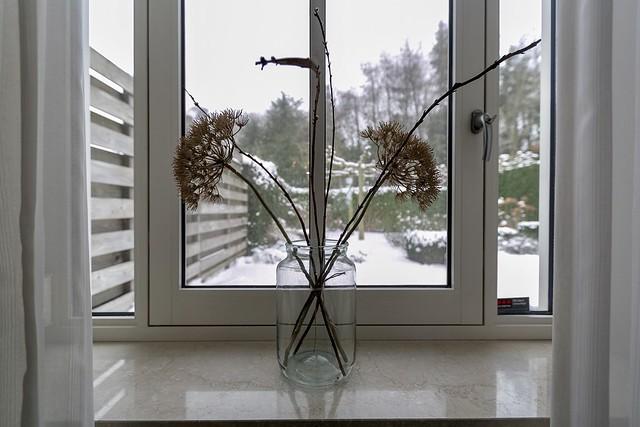 Glazen fles met takken vensterbank