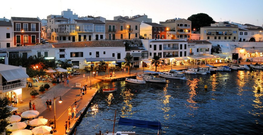 A view of a seafront village on the island of Menorca. White houses along side a promenade. Boats on the sea anchored on the other side of the promenade. Spain.