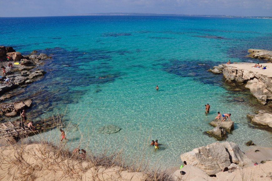 View of a rocky beach on Formentera Island, Spain, with peopel swimming in the azure colored sea.