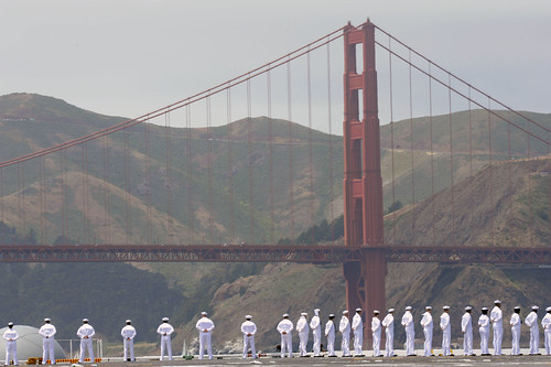 Sailors aboard USS Nimitz man the rails as it passes under the Golden Gate Bridge. by Official U.S. Navy Imagery