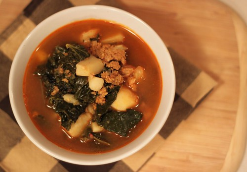Top-down view of a bowl of soup with a reddish broth, lots of kale and potatoes, and crumbled veggie chorizo.