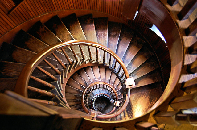 View down wooden oval spiral stairs that are well worn.
