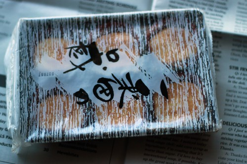 Top-down shot of a carton of mochi, wrapped in plastic packaging with Japanese characters. The mochi is under plastic, and each piece sits in a little red wrapper.