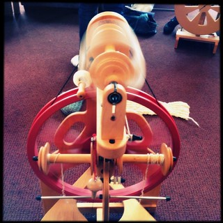 A point-of-view shot of a Schacht Ladybug double-treadle spinning wheel in action