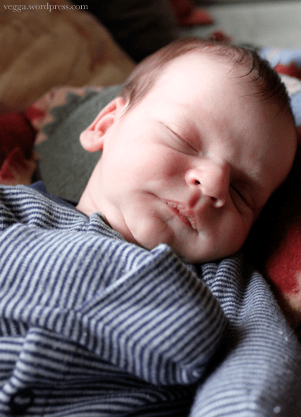 A sleeping baby wearing a striped onesie with built-in hand covers.