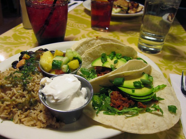 Plate filled with three tacos, rice and beans, and two small metal bowls of vegan sour cream and pico de gallo.