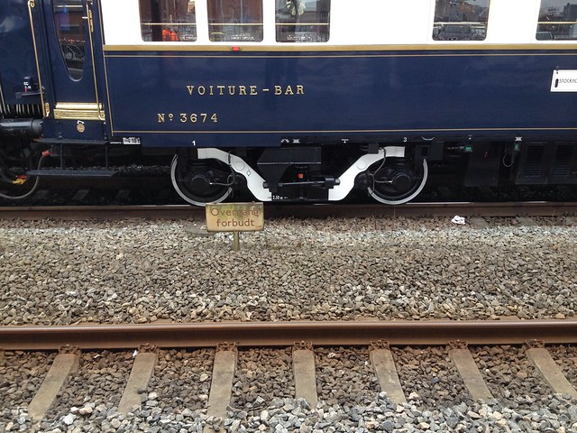 Modern bogie on a vintage train and a vintage sign on a modern station
