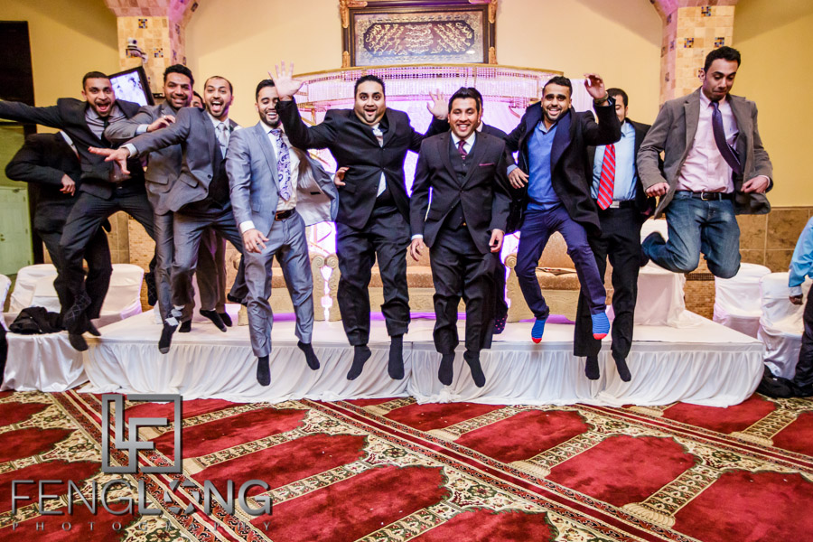 Groom and groomsmen jumping off the stage after wedding ceremony