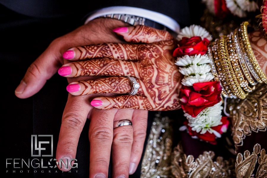 Bride and groom's hands showing rings and bridal mehndi henna design